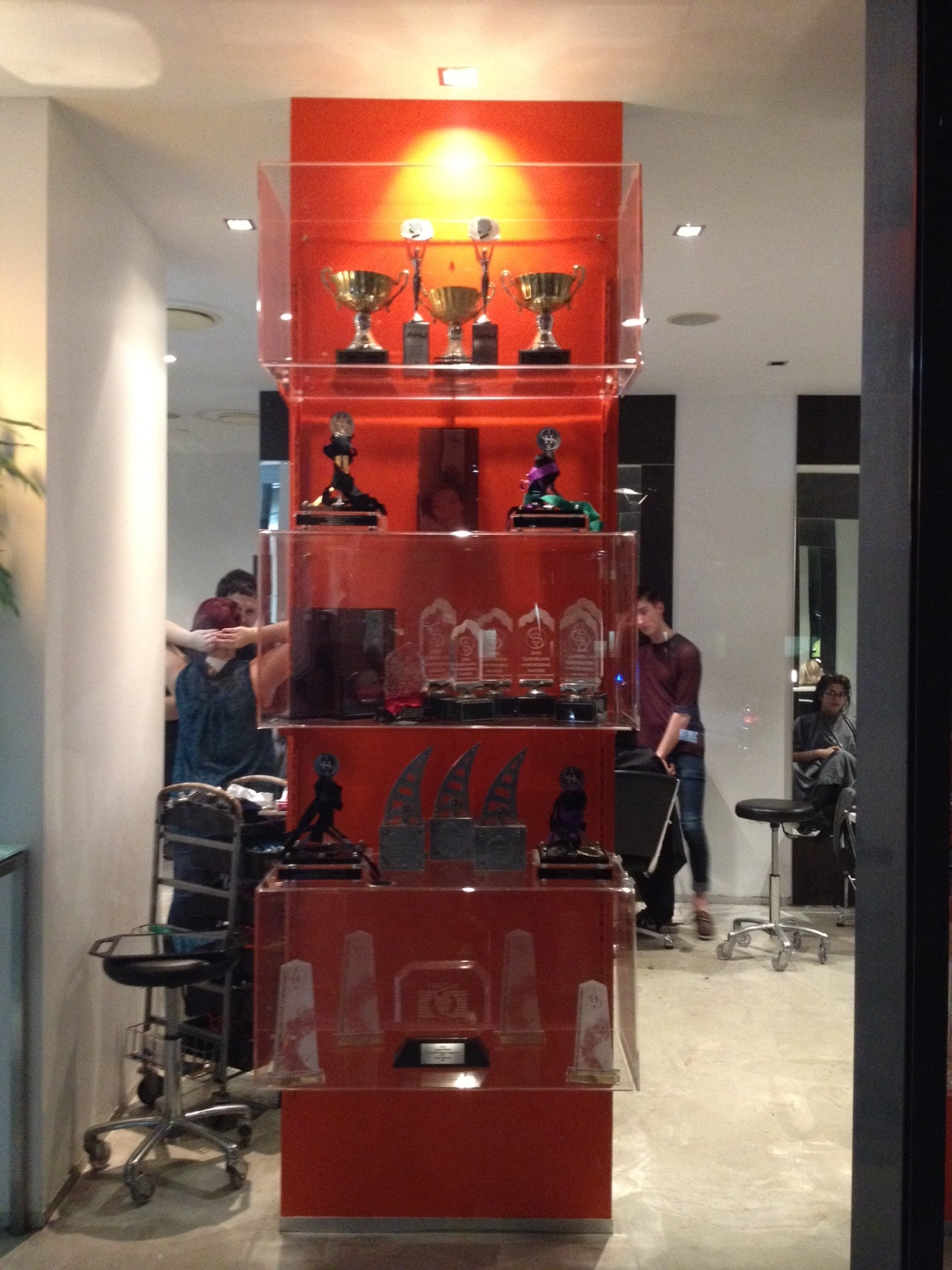 Great Visual merchandising by the VM+ team. Panels of orange and loads of trophies by Carole Haddad - legend hairdresser