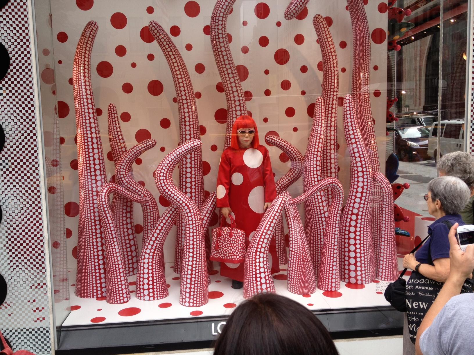 Yayoi Kusama standing in Louis Vuitton window New York, 2012