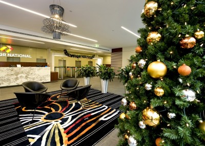 Christmas tree display corporate office foyer gold copper silver baubles with swag garland